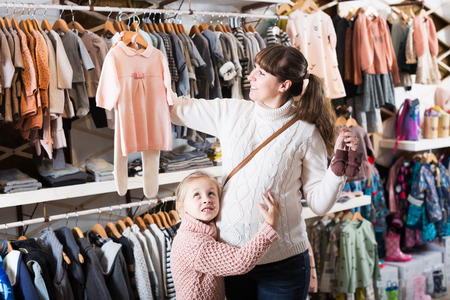 Positive pregnant mother and daughter choosing clothes for baby in children's cloths store