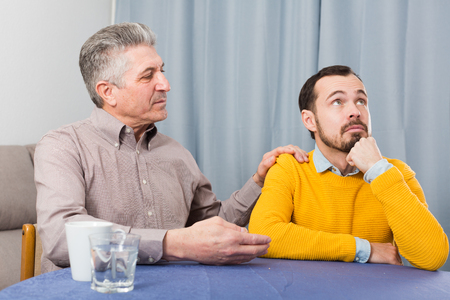 Mature father and son are serious talk and solve family problems at home