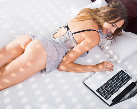 young sexy woman in underwear lying in bed with laptop