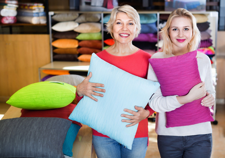 Happy cheerful positive girl and mature woman customers showing bought pillows in home textile shop