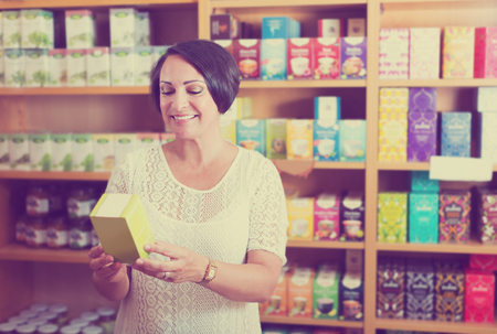 Portrait of positive mature woman with biologically active dietary supplements package in store
