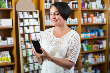 Glad mature woman customer holding mobile phone and choosing goods in healthy food store