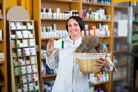 woman seller 50s  in uniform holding bunch of dried herbs in pharmaceutical store