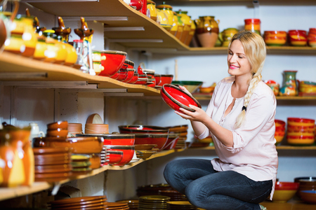 Portrait of glad charming smiling woman choosing glazed with red color ceramic utensil in boutique