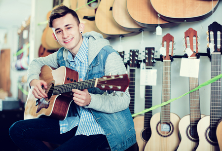 Smiling male teenager examining various acoustic guitars in guitar shop