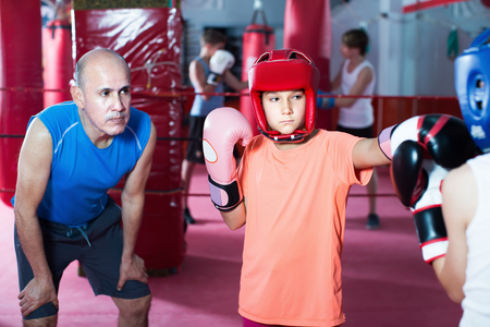 Young girl sparring at boxing workout with coach on boxing ring