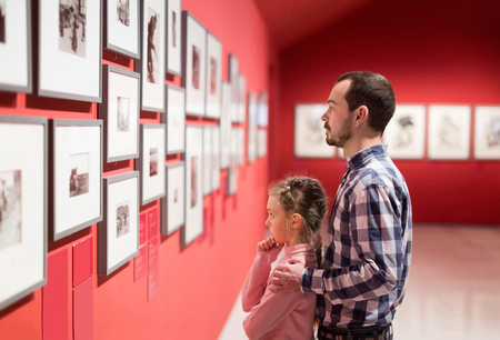 Foto de positive father and daughter looking at exhibition of photos in museum - Imagen libre de derechos