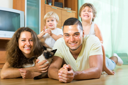 Happy father, mother, a cat and two children laying on the floor and smiling