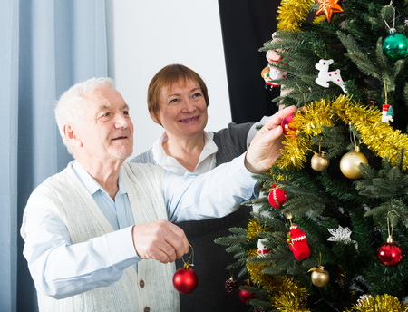Elderly couple preparing to celebrate in his home Christmas and New Year