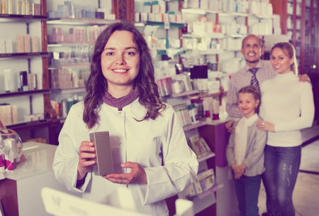 Cheerful diligent pharmacist in white coat working the pharmaceutical store and consulting customers