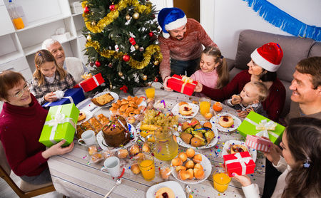 Large satisfied family exchanging gifts during Christmas dinner