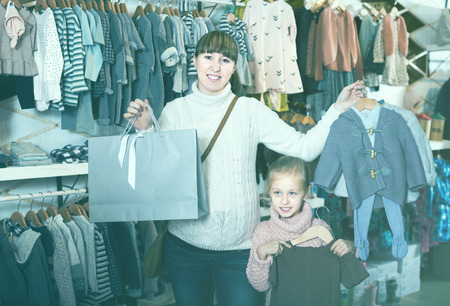Positive pregnant woman and child enjoying purchases in children's cloths store