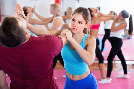 Glad cheerful positive smiling female is training self-defence moves in pair with trainer in sporty gym.