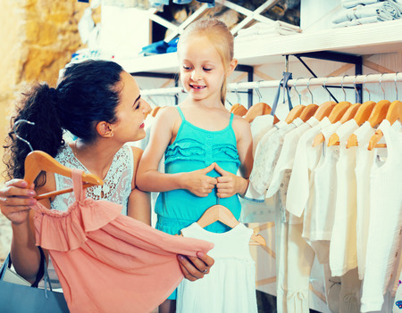 portrait of european glad woman and girl shopping white baby apparel in clothes store