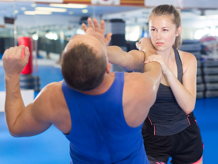 Adult woman is fighting with trainer on the self-defense course for woman in sport club