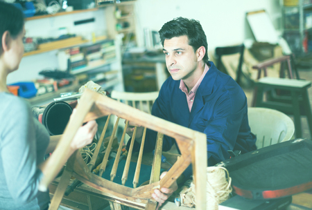 Polite master carpenter taking from young woman broken chair for repair