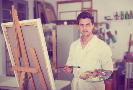 Happy art painter holding artist palette and painting on canvas