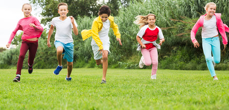Photo pour Smiling kids are jogging together in the park and having fun. Focus on girl - image libre de droit