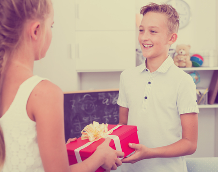 Sister is given to brother a box with surprises at celebrate his birthday.