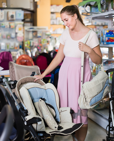 joyous pregnant female looking for baby carriage from assortment at kids shop