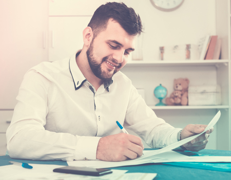 Smiling happy young man signing profitable financial agreement at home