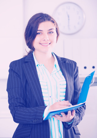 Female manager is signing agreement papers of financial nature at office.