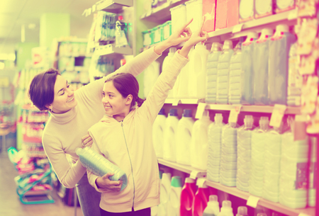 Young woman customer with girl looking for a cleaners for home in a supermarket. Focus on both persons