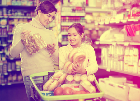 Cheerful female shopper with teenage daughter searching for bread in supermarket