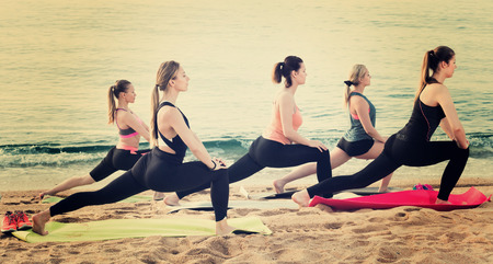Group of glad females performing yoga on sunny seaside