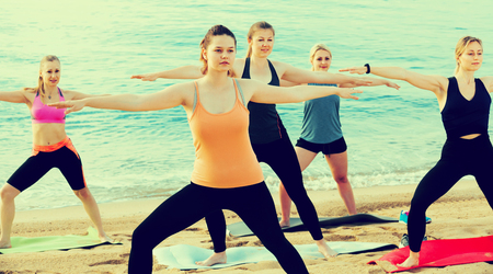 Young slender women exercising yoga poses on sunny beach by ocean