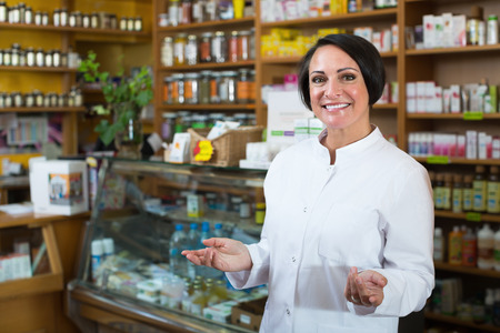 Glad mature female seller in uniform standing with dietary supplements in pharmaceutical  store
