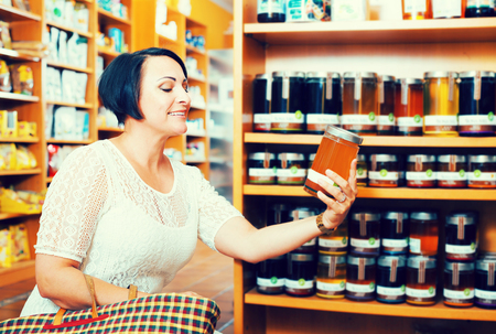 Portrait of smiling mature woman choosing different kinds of natural honey in healthy food store