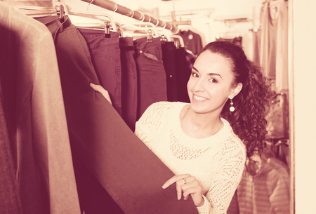 Smiling young female customer selecting new breeches at the store