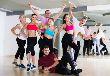 Happy males and females dancing excited posing in studio