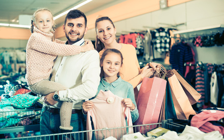 Portrait of young happy parents with two girls during family shopping