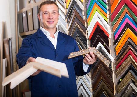 Photo pour man seller standing in picture framing studio with wooden details  - image libre de droit