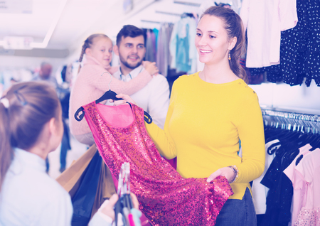 Cheerful mother with little girl choosing evening dress in clothing shop