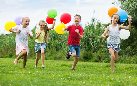 Photo for Happy girls and boy running all together  with multicolored balloons in backyard - Royalty Free Image