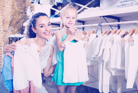 Smiling cheerful woman with small girl choosing white baby clothes in kids apparel boutique