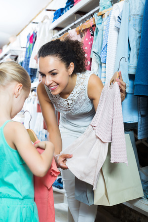 Positive adult mother with daughter buying pink dress in pink color in shop