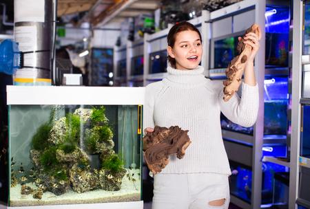 Happy cheerful  girl in aquarium store choosing brown petrified wood for aquarium installation