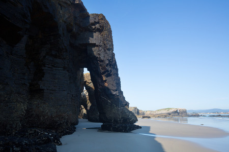 Natural arches at sand beach in  sunny day. As Catedrais beach - Cantabric coast  of Spain