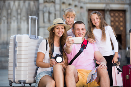 Active parents with two kids taking selfie near city sights