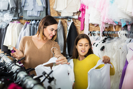Young mother and daughter choosing pretty dress in children's cloths store