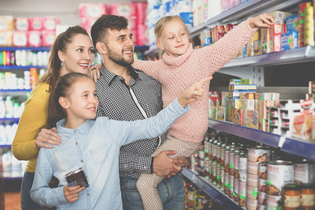 Happy  positive smiling family with two little girls buying food products in supermarket