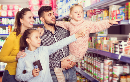 portrait of young glad family of four shopping together in grocery store
