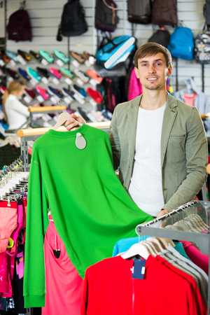 Positive young man choosing a sporty jacket in the store