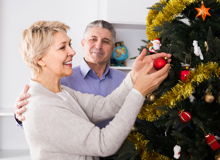 Mature happy english couple preparing to celebrate in his home Christmas and New Year