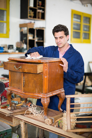Adult craftsman inspecting old nightstand before restoration in workshop