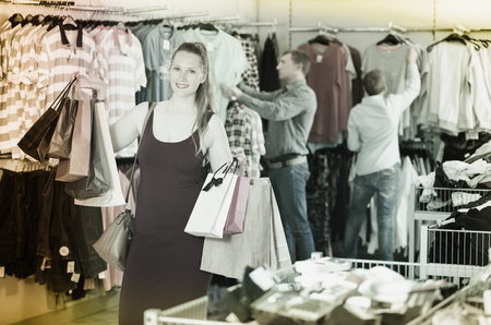 positive woman  displaying shopping bags with purchase in the shop